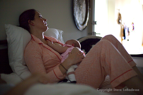 Mother breast feeds her infant early in the morning.