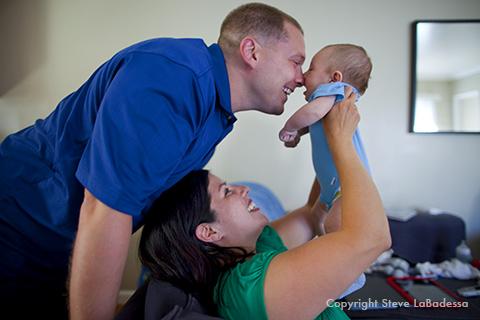 Mom and dad play with their infant son at home.