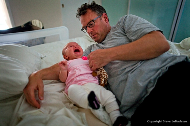 Dad calming crying infant daughter.