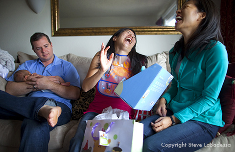 Dad holds the newborn infant. Mom recieves gifts from a family friend at home.